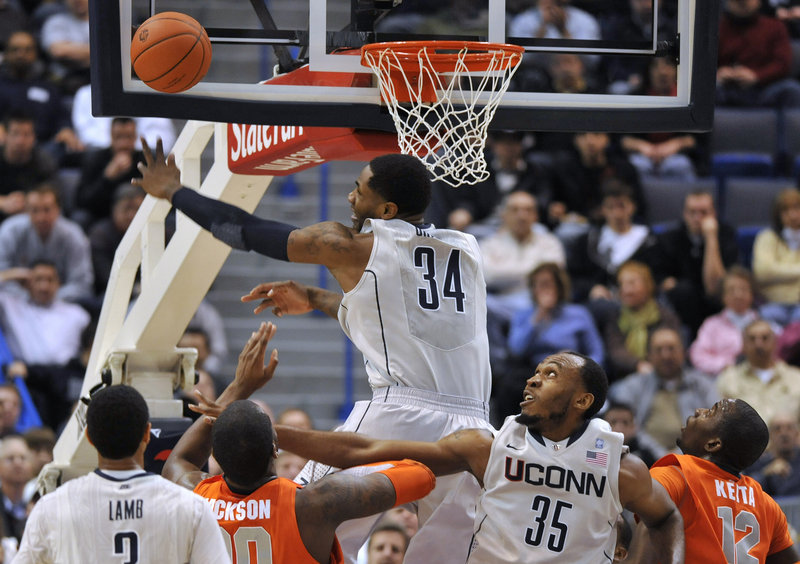 Alex Oriakhi of Connecticut swats away a shot by Syracuse's Rick Jackson, second from left, as Connecticut's Charles Okwandu, 35, defends during the first half of Syracuse's 66-58 win Wednesday night at Hartford, Conn.