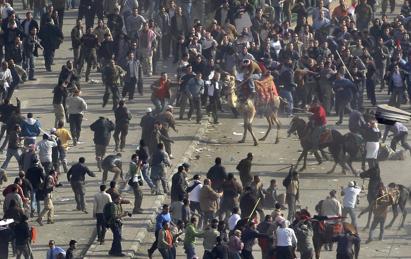 Pro-government demonstrators, below, some riding camels and horses and armed with sticks, clash with anti-government demonstrators, above, in Cairo's Tahrir Square. Live television images showed people rushing from the scene with bloodied limbs and skulls.