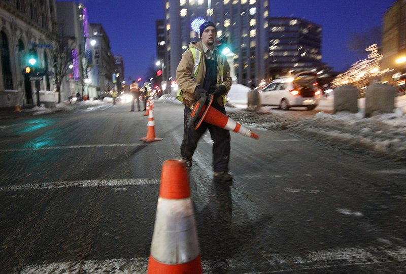 A Unitil worker lays down cones Thursday evening after a gas leak forced the closure of one lane of Congress Street near the intersection of Preble Street in Portland.