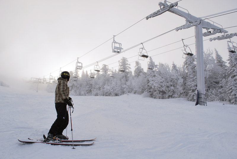 A skier rests near a section of the Spillway East chairlift, in foreground, in the days after a cable derailed and some skiers fell to the ground. The chairs were covered with snow and ice while engineers tested the equipment.