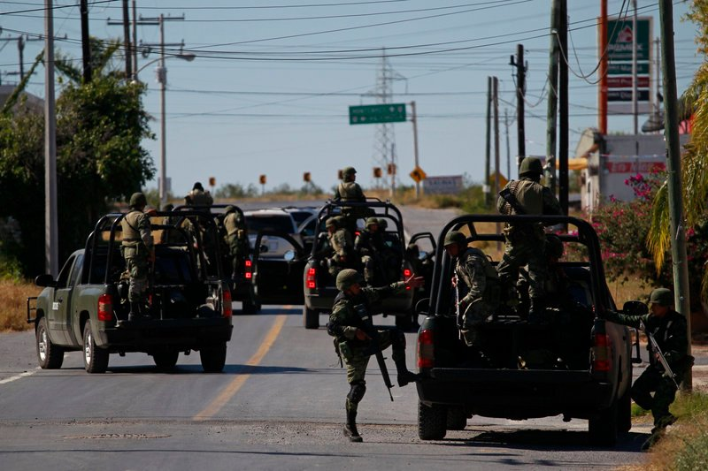 Mexican soldiers leave after inspecting a home in Ciudad Mier, Mexico in November. Tactics used by drug gangs are often similar to those used by soldiers in combat, observers say. Mexican gangs are now hybrids of mafia, insurgency and terrorist groups, said Mexican writer Sylvia Longmire.