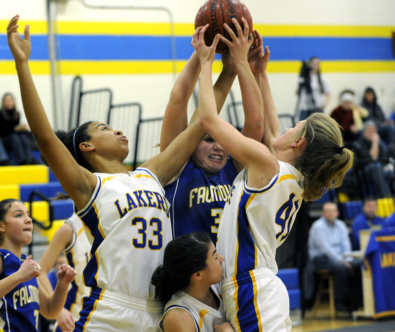 Jenna Serunian of Falmouth attempts to control a rebound Friday night while sandwiched by Tiana-Jo Carter, left, and Kelsey Winslow of Lake Region during Lake Region s 49-33 victory at Naples.