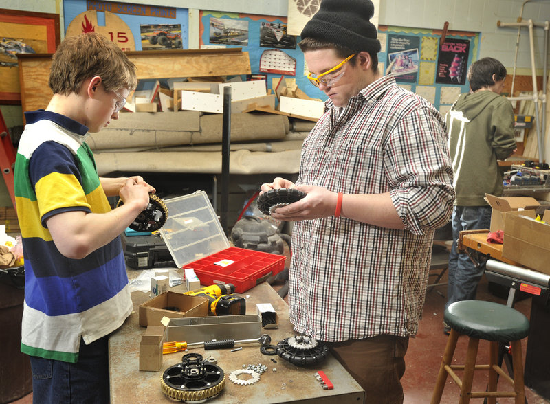 Team members Ross Usinger, left, and Garrett Libby assemble wheels for the robot.