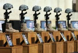 Helmets on rifles and photos of the victims mark a memorial service for the 13 people killed at Fort Hood.