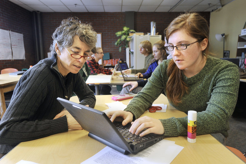 Teacher Susan McCray works with humanities student Annie Laughlin on Monday at Casco Bay High School in Portland. A recommendation to boost enrollment coincides with the school's second lottery to select the next freshman class from an overflow list of eighth-grade applicants.