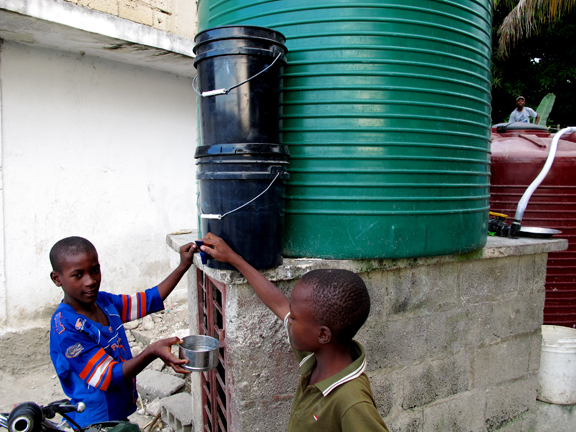 Two children check the water coming through the new filtration system.