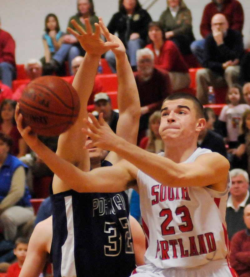 South Portland s Vukasin Vignjevic drives to the basket as Portland s Mike Herrick moves in Tuesday night at Beal Gym. Portland completed a two-game sweep of the Red Riots.