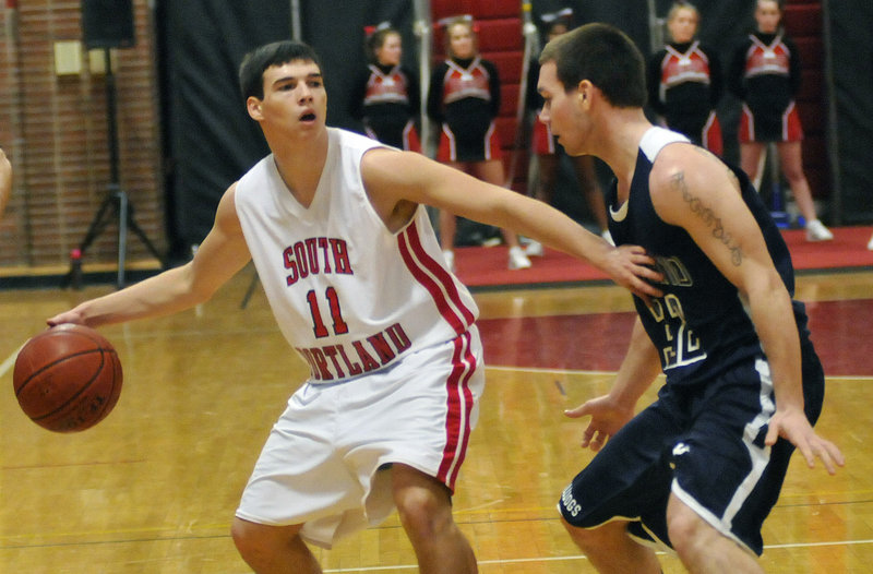 South Portland s Steve Hodge, left, holds off Portland's Mike Herrick while looking for an open teammate Tuesday night at South Portland. The Bulldogs won, 59-54.
