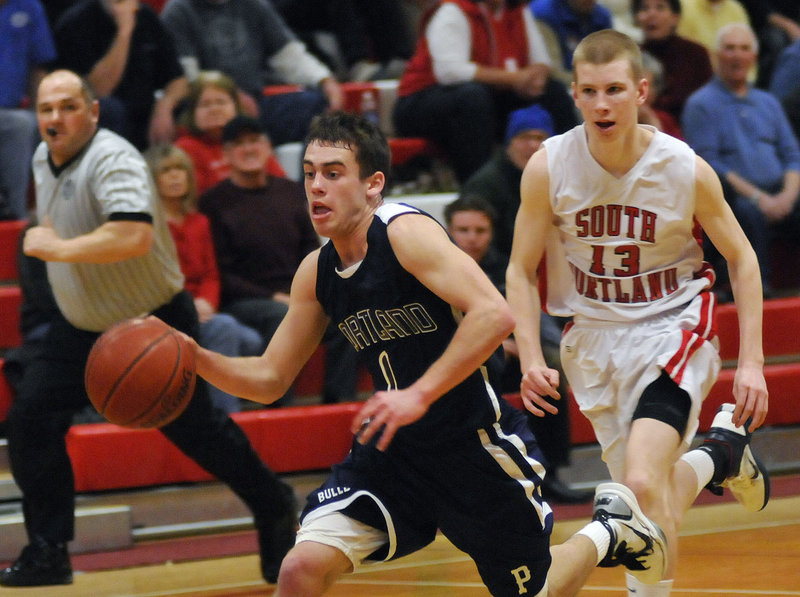 Portland s Nick Volger drives to the basket as South Portland s Tanner Hyland follows him Tuesday night in South Portland. The Bulldogs held off the Red Riots to win their fourth straight.