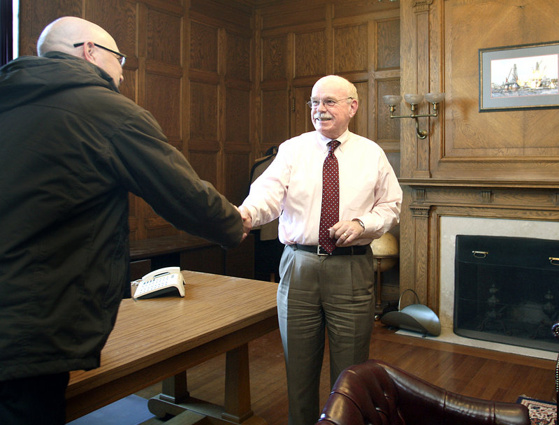 Eric Labelle, left, Portland's assistant director for the department of public services, says goodbye to Joe Gray, retiring Portland city manager, in his office at City Hall on Thursday. According to Gray, Portland has benefited by building its economic ties to tourism and biotechnology.