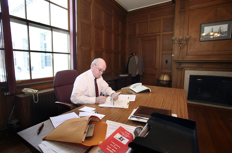 Joe Gray, retiring after 10 years as Portland's city manager, takes care of some final paperwork in his City Hall office on Thursday.