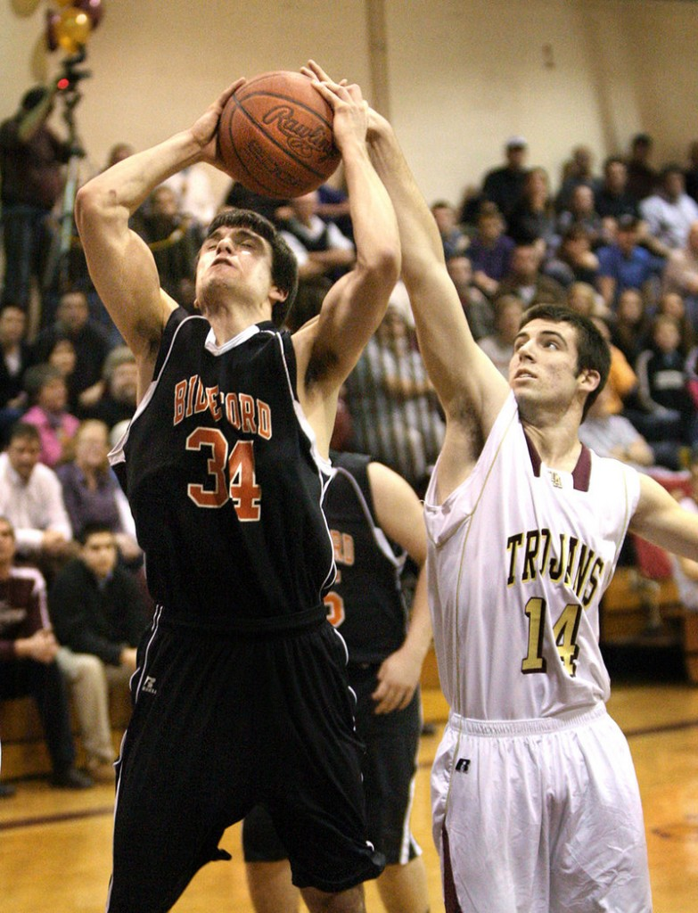 Chance Baldino of Biddeford, left, has his shot blocked by Josh Woodward of Thornton Academy during the first half Thursday night. Thornton won 72-70 in double overtime.