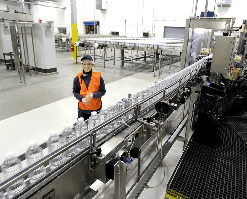 Production technician Louise MacGregor keeps a eye on a line of just-filled bottles at the Poland Spring bottling plant in Hollis. Some machines can fill 1,200 bottles per minute.