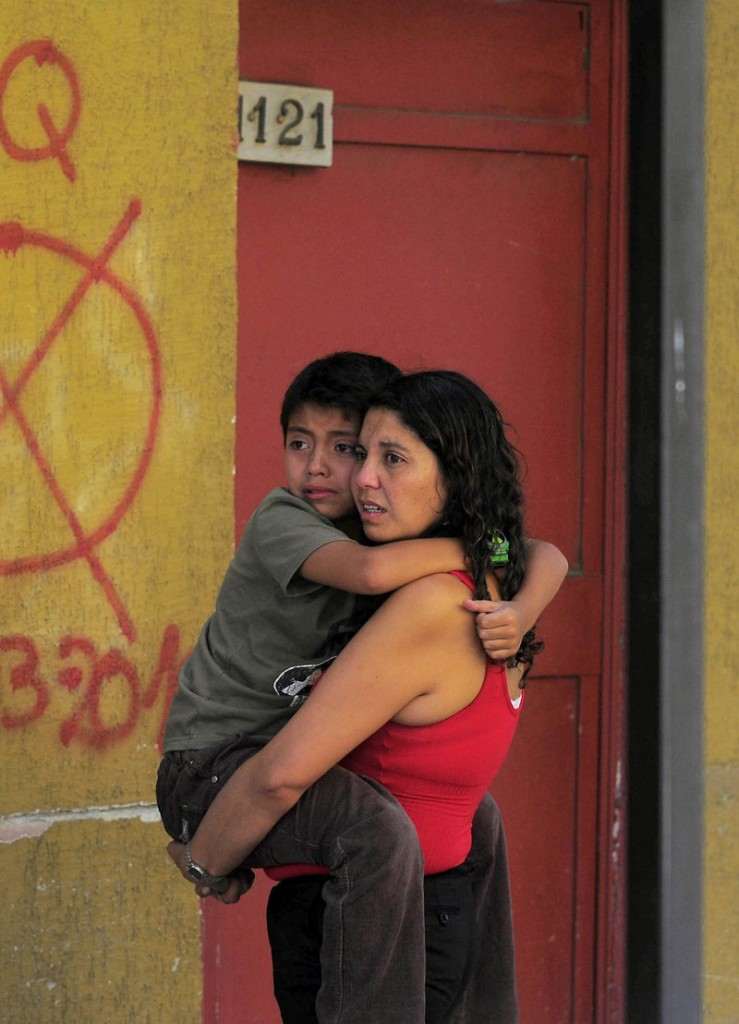 A frightened woman and child evacuate a building as a precaution after a magnitude-6.8 earthquake struck in Concepcion, Chile, on Friday.