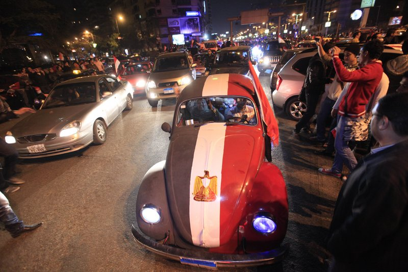 A Volkswagen Beetle, left, is painted in the colors of the Egyptian flag in the capital city during the raucous celebrations Friday.