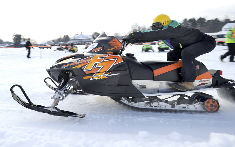 A snowmobile racer zooms across the ice in a radar run Saturday at the Naples Winter Carnival, which continues today.