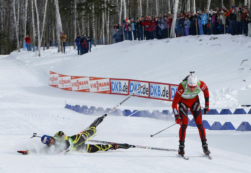 Martin Fourcade of France tumbles as he tries to beat Norway's Emil Hegle Svendsen to the finish line in the 12.5-kilometer pursuit Saturday in the World Cup biathlon at Fort Kent. A finish-line photo showed Svendsen's ski getting there first.