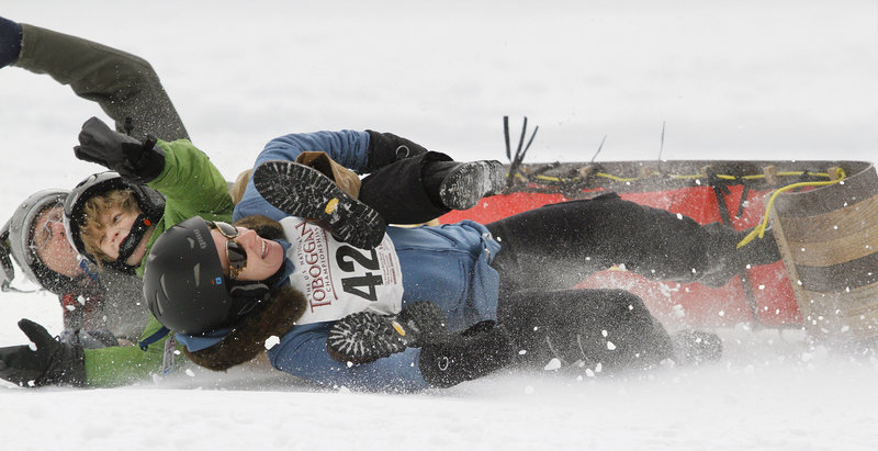 Team TNT, consisting of the Tanner family from New York City, wipes out at the end of the run during the 21st Annual U.S. National Toboggan Championships in Camden Saturday.