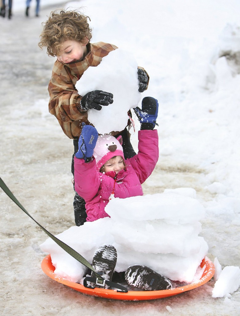 Torin Svedlow, 4, of Falmouth stacks chunks of snow on his 2-year-old sister Helen.