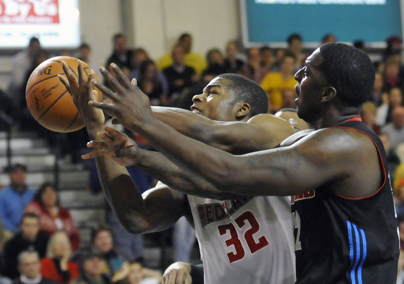 Deshawn Sims, left, of the Maine Red Claws stretches past Jamar Brown of Springfield to reach for a rebound during Maine's 97-96 win on Sunday at the Portland Expo.