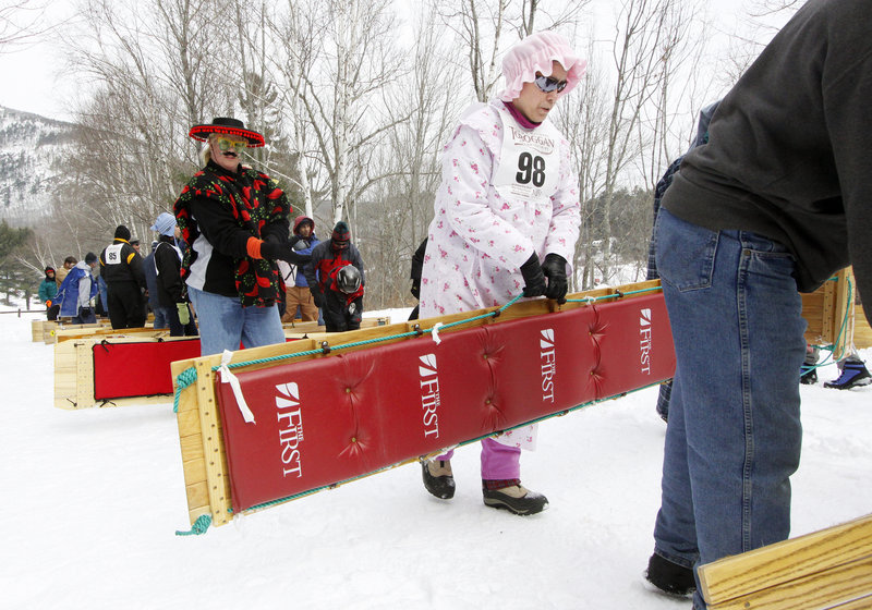 Patti Gwara of Bristol carries her sled up the hill on Saturday. Her two-person team is named Chute My Ash Is Dragon.