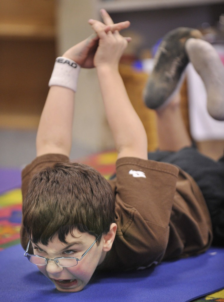 Danny Tocci works on a position during a yoga class at Riverton Elementary School.