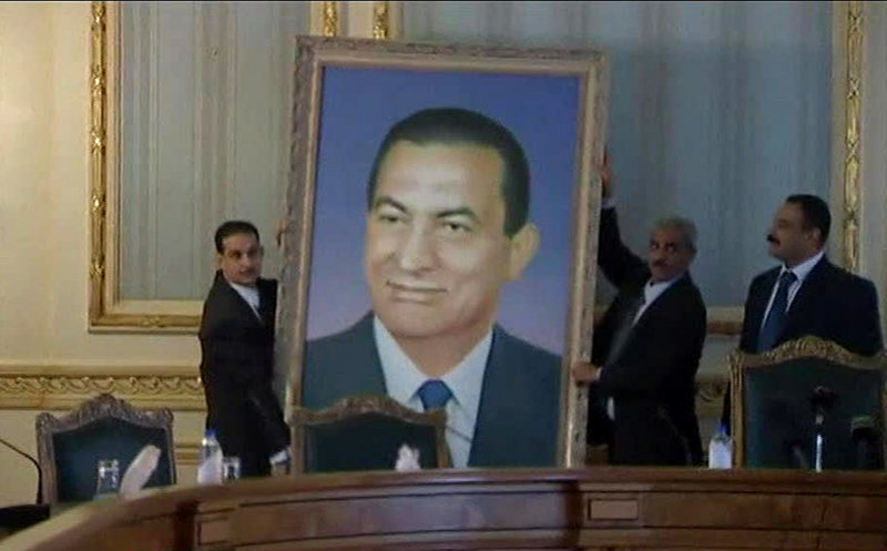 Officials remove a huge framed portrait of ousted Egyptian President Hosni Mubarak from the meeting room at the main Cabinet building in Cairo on Sunday. Egyptians are taking down images of Mubarak that have hung in public and private institutions throughout his three decades in power.