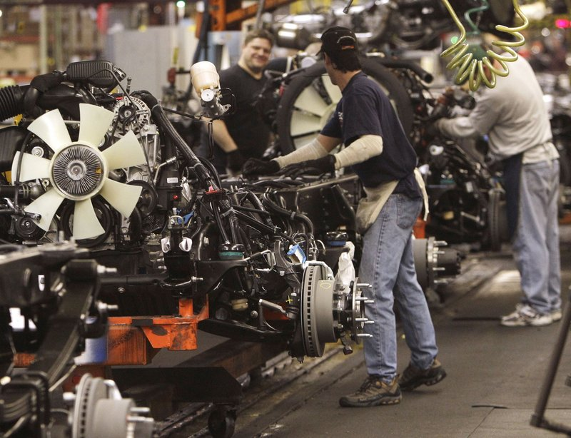 Workers attach engines to chassis for Silverado and Sierra pickups at the GM assembly plant in Flint, Mich. GM disclosed Monday that it will pay $189 million in bonuses to 48,000 U.S. hourly workers.