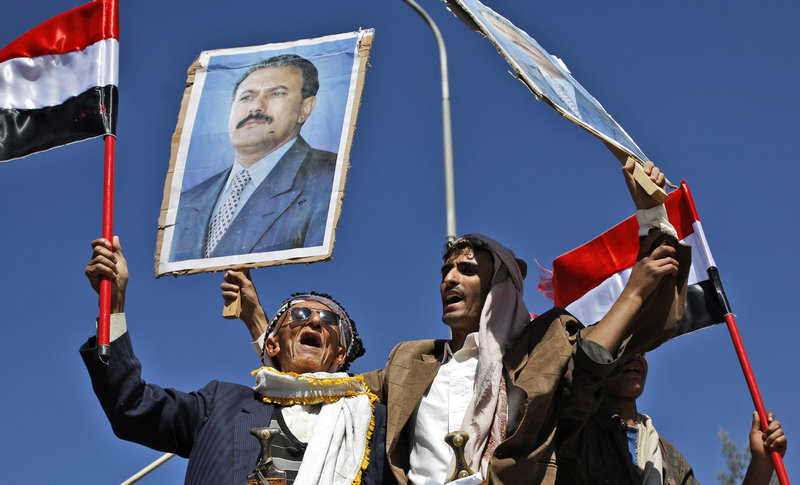 Supporters of the government wave flags and raise posters of President Ali Abdullah Saleh in Sanaa, Yemen, on Tuesday, while a thousand anti-government protesters also marched.
