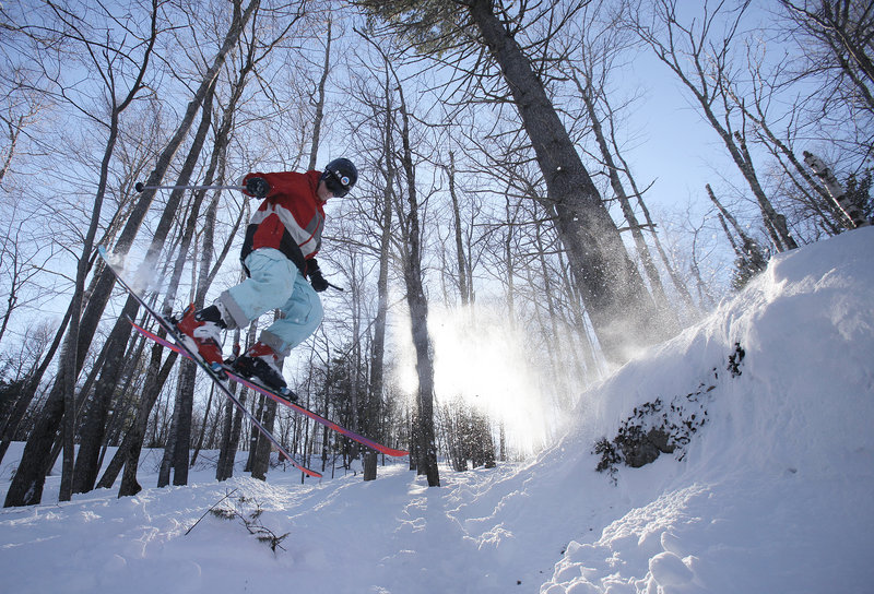 Derek Drechsler skis off a snow-covered rock. The mountain added three new glades this past fall.