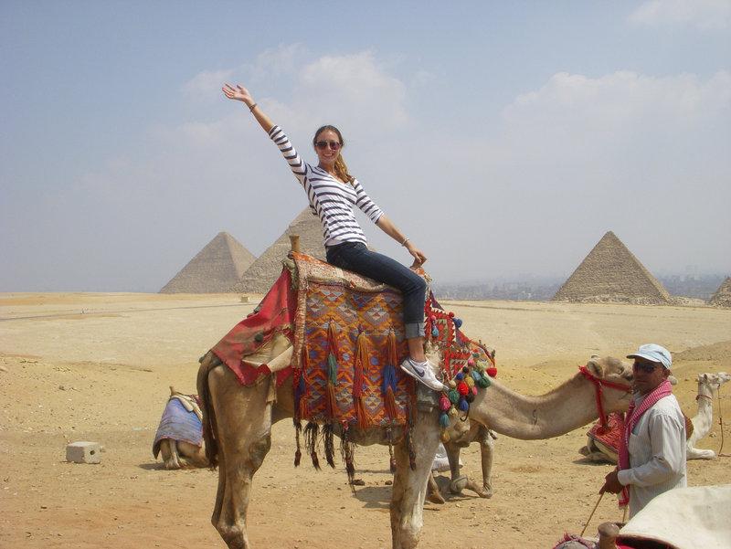 Maja Bedak, a University of Maine student from Portland, rides a camel near the pyramids in Egypt while studying last semester at The American University in Cairo.