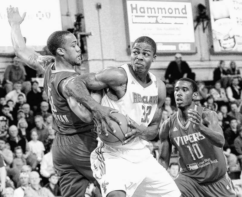 DeShawn Sims, who scored 30 points Thursday for the Red Claws, moves against Patrick Sullivan, left, and Terrel Harris of the Rio Grande Valley Vipers in the Vipers 107-101 victory.