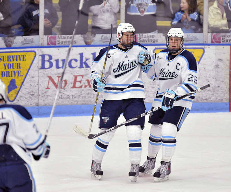 Josh Van Dyk, left, and Tanner House celebrate after Van Dyk scored in the first period – his first goal of the season – to give Maine a 2-0 lead.