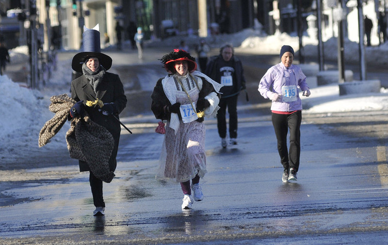 In period costumes, Mike Miller and Laura Jean Wilcox, both of Seattle, run toward the finish line during the February Frostbite 2.5K in Portland on Saturday. The couple were visiting Wilcox's parents, who are members of the Longfellow Chorus.
