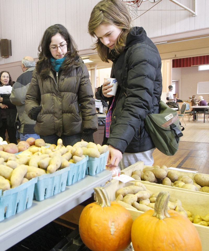 Reva Eiferman, left, and Emily Thielmann check out produce from Buxton's Snell Family Farm during a CSA fair in Portland.
