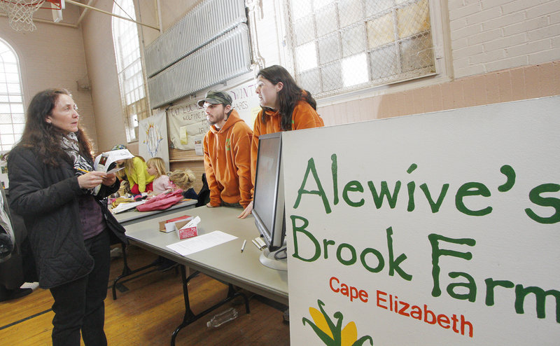 Jessie Grearson of Falmouth talks to Lincoln Jordan and his sister Caitlin Jordan of Alewive's Brook Farm in Cape Elizabeth during a community-supported agriculture fair Sunday at Woodfords Church. Alewive's Brook also allows CSA members to use their credits to buy lobsters.