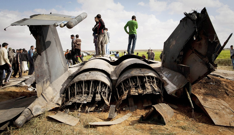 Libyans inspect the wreckage of a US F15 fighter jet after it crashed in an open field in the village of Bu Mariem, east of Benghazi today. The U.S. Africa Command said both crew members were safe after what was believed to be a mechanical failure of the Air Force F-15. The aircraft, based out of Royal Air Force Lakenheath, England, was flying out of Italy's Aviano Air Base.