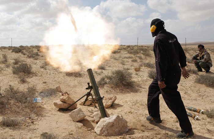 A Libyan rebel shells pro-Gadhafi forces with mortar fire today, along the front lines outside the eastern town of Brega, Libya. Libya conceded today that Foreign Minister Moussa Koussa had resigned but claimed that it was a personal decision driven by health problems, not a sign that the embattled regime is cracking at the highest levels.