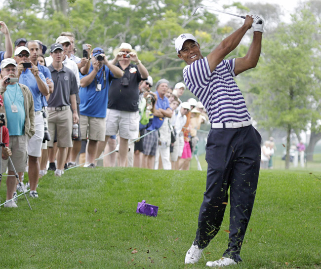 Tiger Woods hits a shot to the eighth green during the Pro-Am competition of the Arnold Palmer Invitational golf tournament in Orlando, Fla., Wednesday.