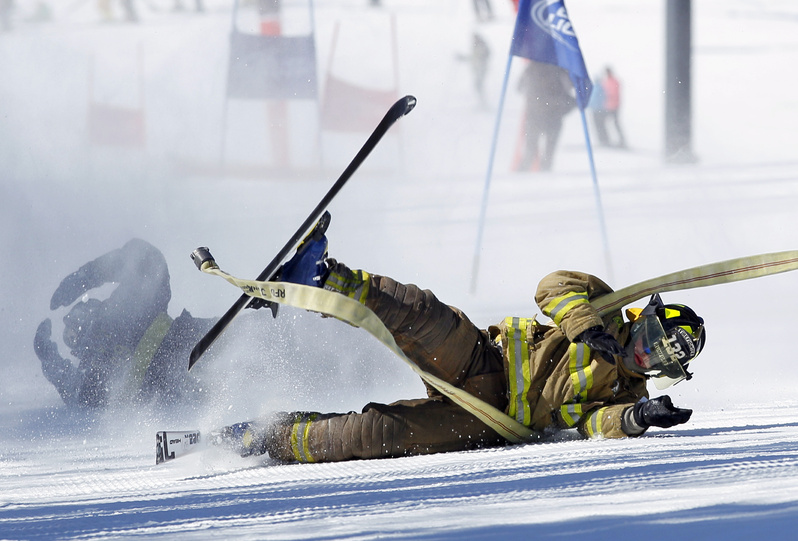 Dalton Bradley of the Rumford fire department crashes during a run in the 21st Annual Firefighter's Fundraising Race today at the Sunday River ski resort in Newry. Teams of five wearing firefighting gear carried a 50-foot hose while negotiating a giant slalom race course. The race benefits the Maine Handicapped Skiing program.