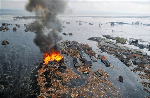 Part of houses swallowed by tsunami burn in Sendai, Miyagi Prefecture (state) after Japan was struck by a strong earthquake off its northeastern coast Friday, March 11, 2011. (AP Photo/Kyodo News) JAPAN OUT, MANDATORY CREDIT, FOR COMMERCIAL USE ONLY IN NORTH AMERICA ?u?J??n?[?v