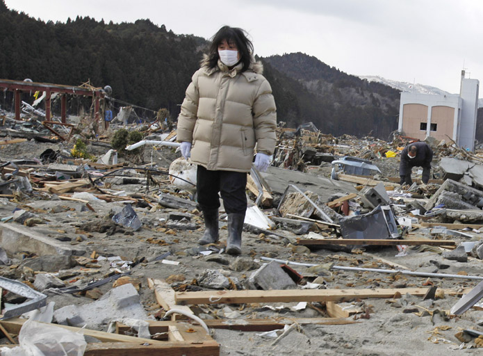 A woman searches for her missing husband through the earthquake and tsunami-hit town of Minamisanriku, Miyagi Prefecture today.