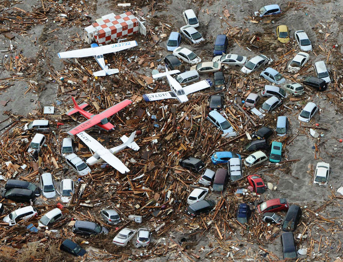 Planes and vehicles sit among the debris after they were swept up in the tsumani that struck Sendai airport in northern Japan today.