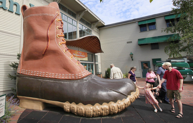 """Shoppers pause at the giant boot outside the L.L. Bean flagship store in Freeport. The company said """"prudent forecasting and cost management"""" allowed it to minimize the impact of soft sales on overall profitability last year."""