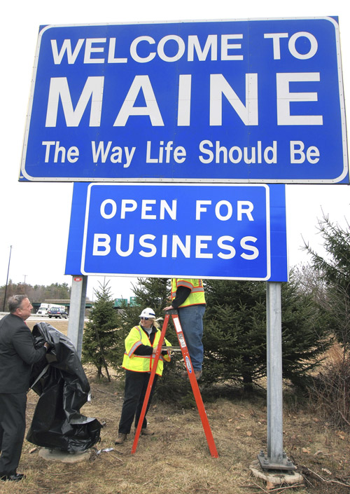 """Gov. Paul LePage, left, unveils a new """"Open for Business"""" sign beneath the """"Welcome to Maine"""" sign along Interstate 95 near the New Hampshire border in Kittery today. Maine Department of Transportation crew supervisors Elaine Cota, center, and Aaron Main, on ladder, assisted."""