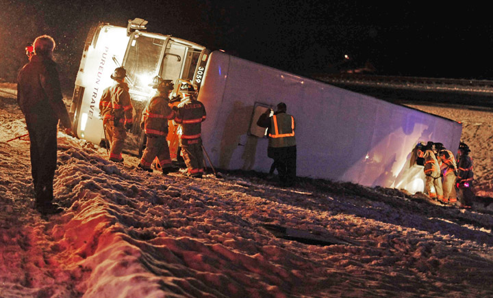In a March 21, 2011, photo, rescue workers examine a tour bus on Interstate 93 in Littlton, N.H. The bus was carrying about two dozen Koreans from Quebec to Boston when the driver lost control on the snowy interstate, injuring 23.