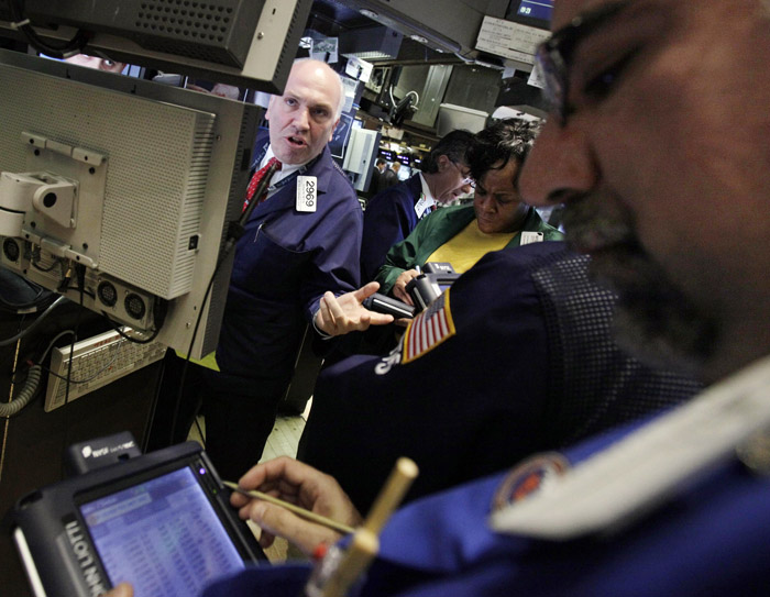 In this photo taken March 15, 2011, specialist Gerard Petti, left, directs trades at his post on the floor of the New York Stock Exchange. (AP Photo)