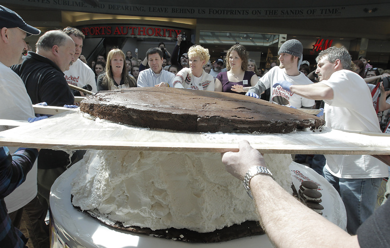 Amy Bouchard, fourth from right, owner of Wicked Whoopies, gets some help putting the 180-pound devil's-food cake top on the 1,067-pound whoopie pie that was assembled at the Maine Mall in South Portland on Saturday. Radio station WMGX and Gardiner-based Wicked Whoopies joined forces to create a pie that would surpass Pennsylvania's 250-pound confection.