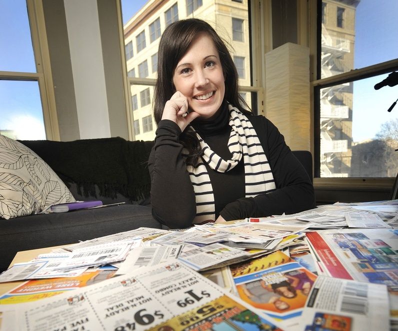 """In this Feb. 1, 2011, photo, Chrystie Corns, an """"extreme couponer,"""" displays some of the coupons she's clipped in her Portland office."""