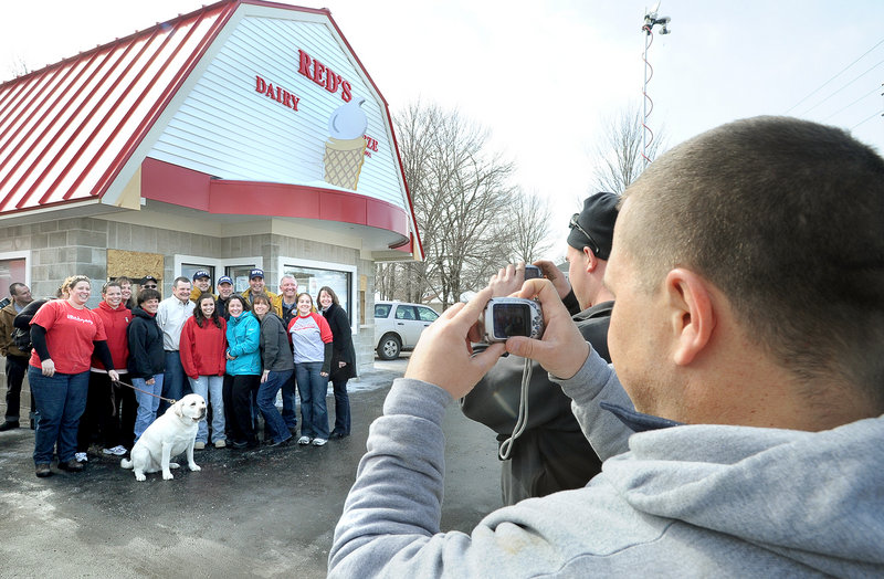 Seth Josef, son-in-law of Red's owner Chris Bolling, takes a photo of family members and past and present workers as the ice cream stand reopened Friday in South Portland.